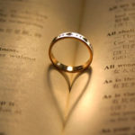 wedding ring sitting in the middle of a book